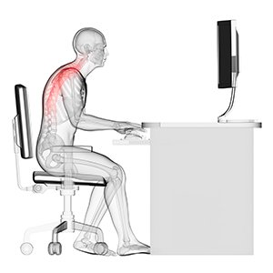 A skeleton showing bad posture at a computer desk