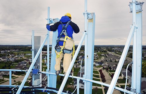 A man working at heights looking at the ground below