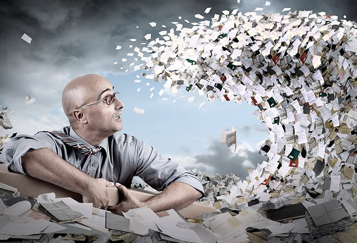Man suffering from stress at work with a tidal wave of paper over him