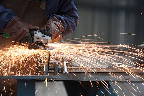 Picture of an angle grinder with sparks. This employee may need health surveillance.