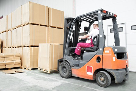 A forklift truck driver moving a pallet