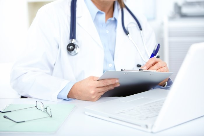 Doctor making notes on a clipboard in front of a computer during a sickness absence occupational health assessment