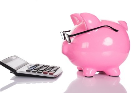 Piggy bank wearing glasses looking at a calculator